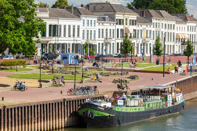 Summer view at the IJssel river and waterside with people relaxing in the sun in the Dutch city of Zutphen, The Netherlands. Zutphen, The Netherlands - July 120 royalty free stock photography