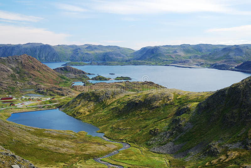 Summer view of Mageroya. Mageroya is an island in Finnmark county in the extreme north of Norway. There are blue fjords and lakes, steep hills overgrown with stock photography