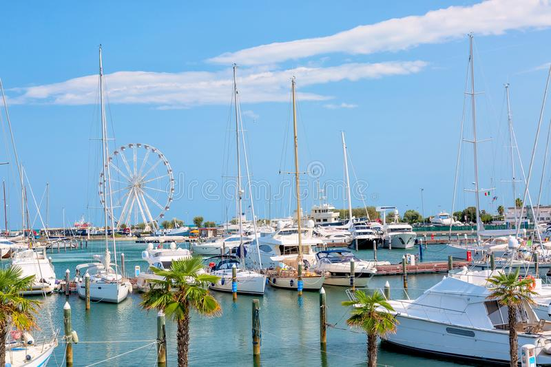 Summer view of pier with ships, yachts and other boats with ferris wheel in Rimini, Italy stock image