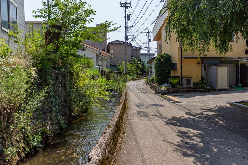 Summer view of small back street with watercourse, downtown Kanazawa, Ishikawa Prefecture, Japan. Summer view of small back street with watercourse, downtown stock images