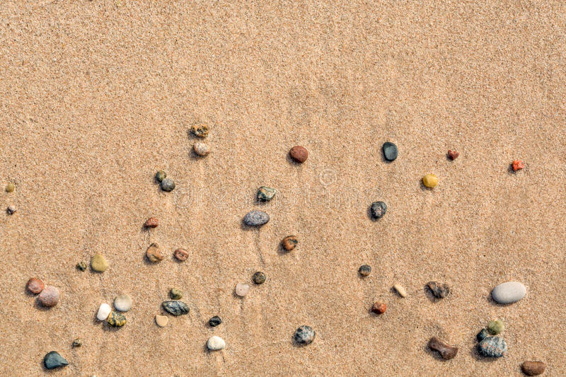 Summer view of small round pebbles on sunny beach. royalty free stock images