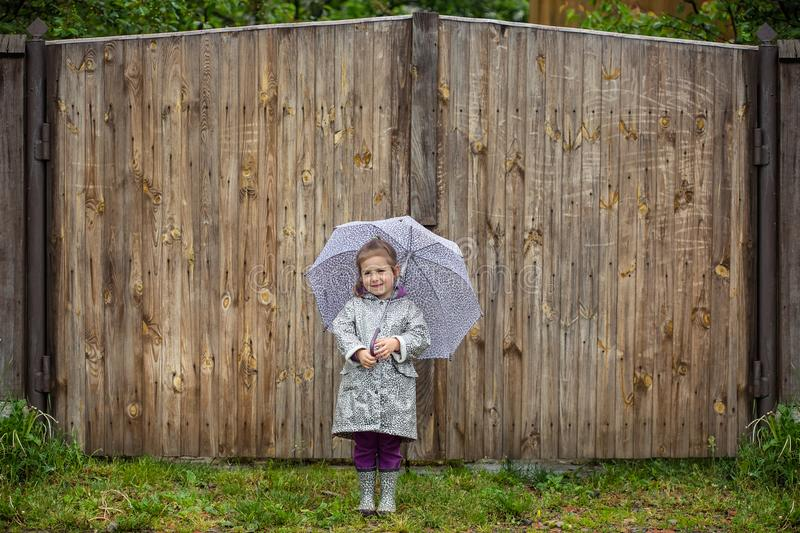 Summer walk in the rain little girl with an umbrella. Puddles royalty free stock photo