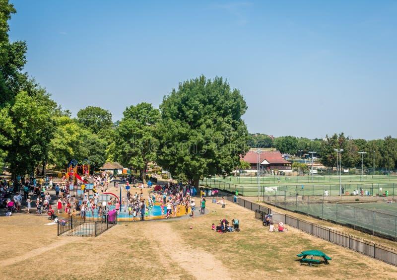 Summer water fun in sprinkler park. Children having fun splashing, spraying and jumping in a pool ground in Wimbledon Sprinkler Park in London stock image