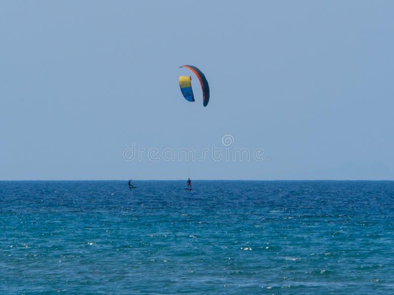 Summer water sports in clear open sea ocean. Summer water sports kite surfing wind surfing in clear sea ocean stock photography