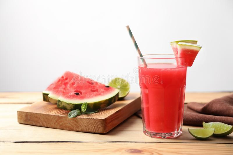 Summer watermelon drink in glass and sliced fruits. On table royalty free stock image