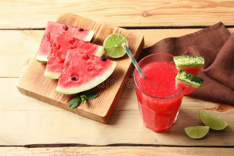 Summer watermelon drink in glass and sliced fruits. On table royalty free stock images