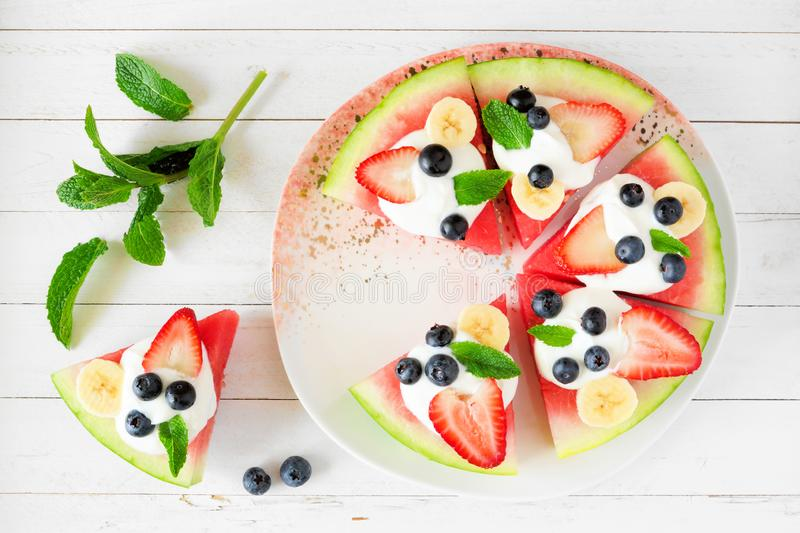 Summer watermelon pizza with blueberries, strawberries, bananas and yogurt, above view over white wood. Summer watermelon pizza with blueberries, strawberries royalty free stock photo
