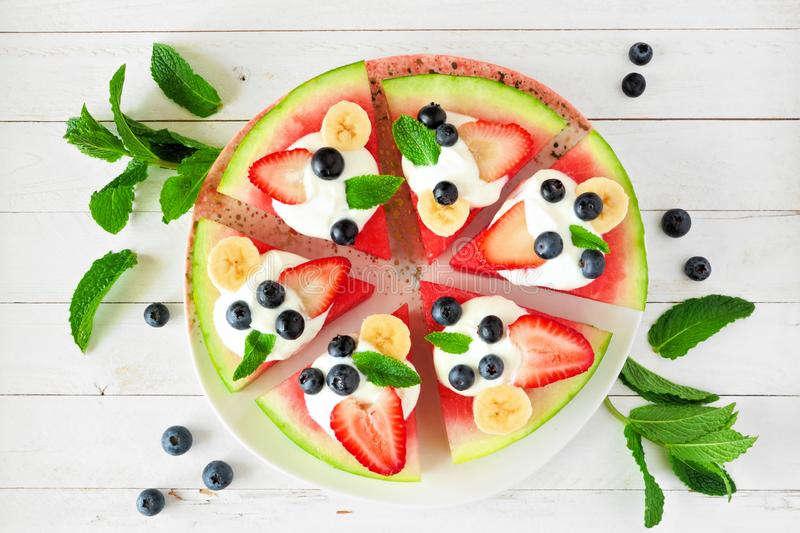 Summer watermelon pizza with blueberries, strawberries, bananas and yogurt, overhead view over white wood. Summer watermelon pizza with blueberries, strawberries stock images