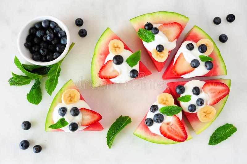 Summer watermelon pizza with blueberries, strawberries, bananas and yogurt, top view over marble. Summer watermelon pizza with blueberries, strawberries, bananas stock photo