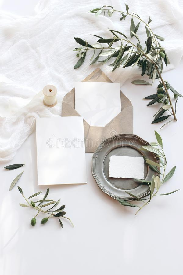 Summer wedding stationery mock-up scene. Blank greeting cards, envelope, vintage silver plate, olive branches and ribbon royalty free stock photos