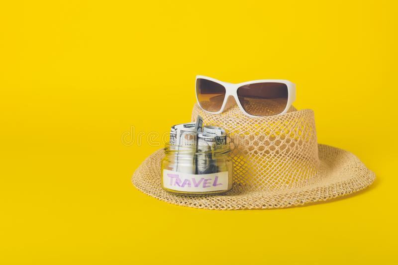 Summer weekend travel vacation concept. Beach accessories, straw hat, white sunglasses and save money glass jar with dollars. Banknotes on yellow background stock photo