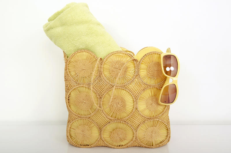 Summer wicker bag with green beach towel and sunglasses. royalty free stock photo