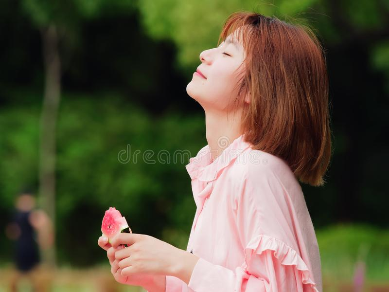 Summer woman holding watermelon slice with eyes closed. Smiling Chinese girl eating watermelon in park. Holiday lifestyle. Brunett royalty free stock photography