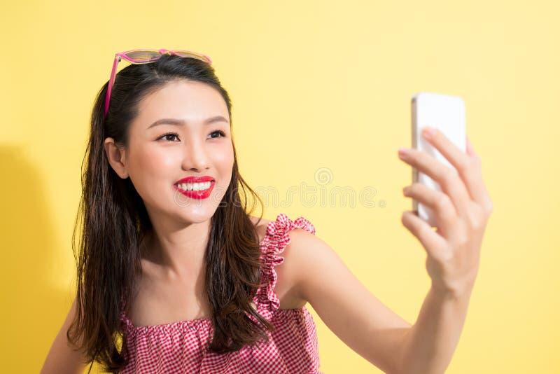 Summer woman taking selfie photo on yellow background. stock photos