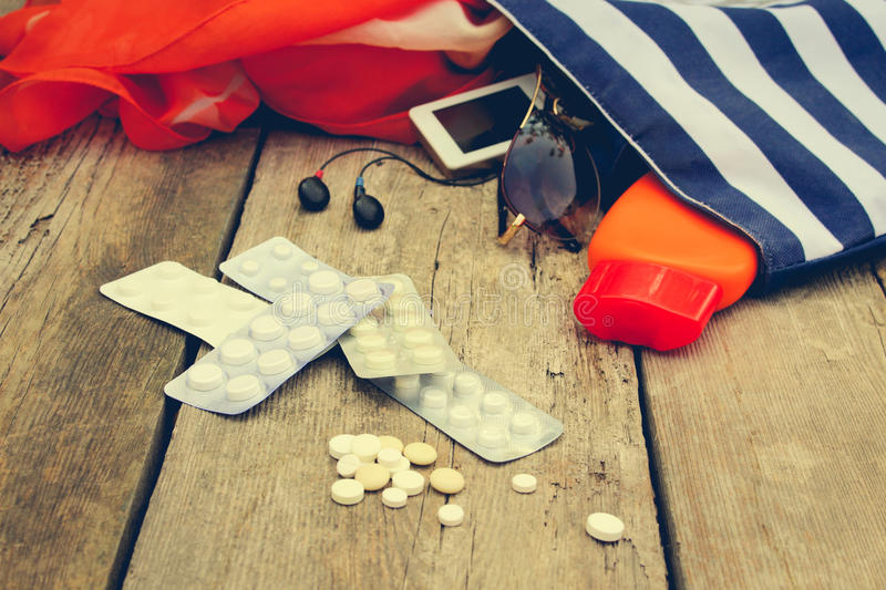 Summer womens beach accessories for your sea holiday and pill. On old wooden background. Concept of medication required in journey. Toned image royalty free stock photos