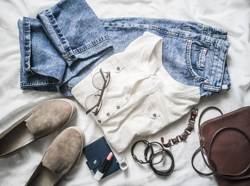 Summer womens fashion clothes set - mom`s jeans, suede sneakers, cotton t-shirt, bag, bracelets, lipstick on a light stock photo