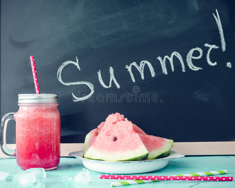 Summer written on the blackboard. With watermelon juice in glass mason jar with slices of watermelon and ice on blue background. Fresh fruit flavored cold royalty free stock photos