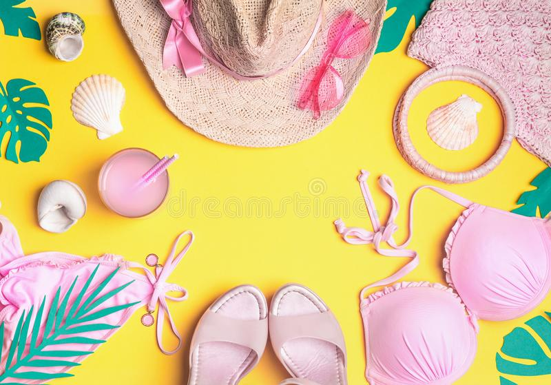 Summer yellow background with pink bikini, straw hat, sunglasses, sandals with cocktail , seashells , tropical palm leaves. Summer stock photo