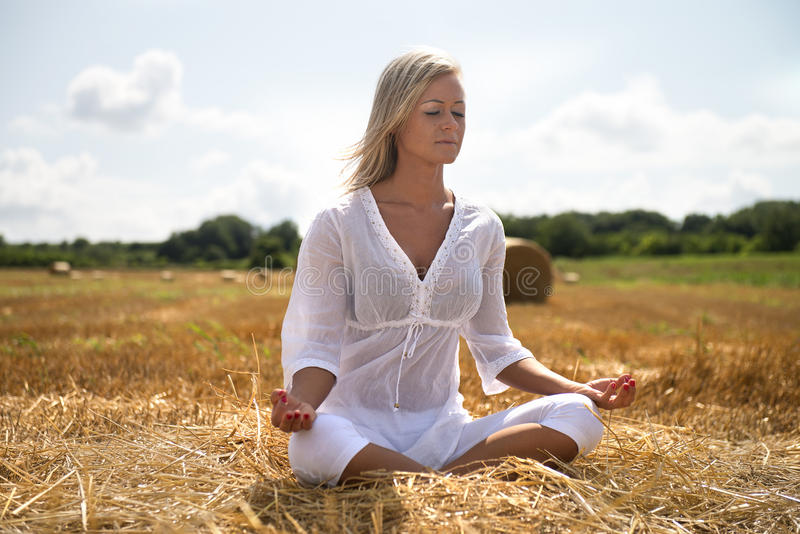 Summer yoga in meadow. Cute young blonde woman does yoga outside in summer in a peaceful farm field