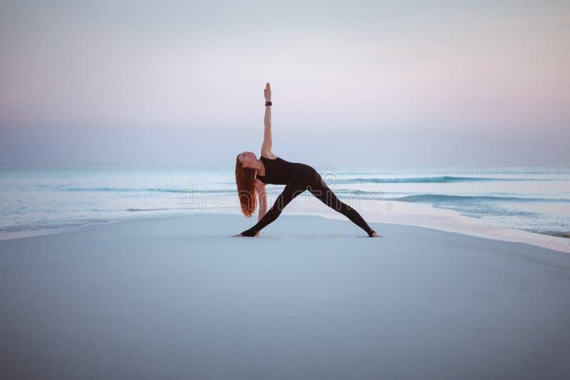 Summer yoga session on a beautiful golden beach of Maldives yoga tour, Trikonasana, triangle pose. Young woman practice balance asanas on Summer yoga session on royalty free stock images