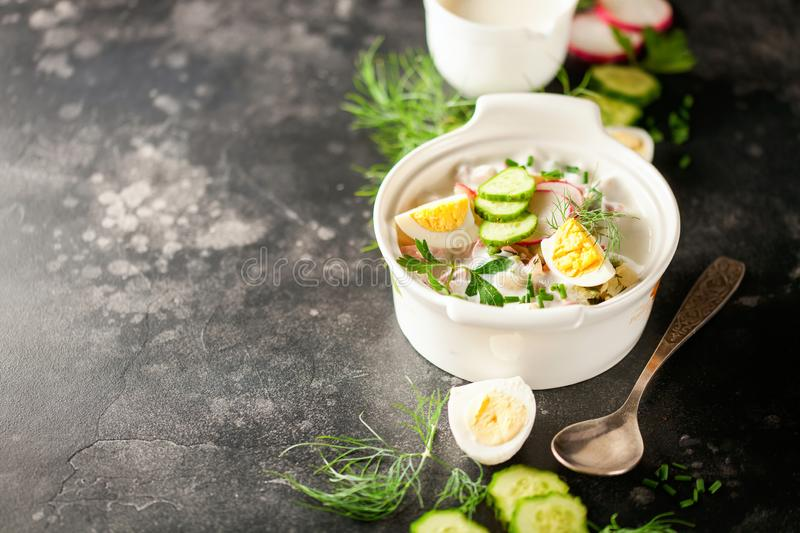 Russian Okroshka. Summer yoghurt cold soup with radish, cucumber, and dill on wooden table. Russian Okroshka. Copy space royalty free stock photography