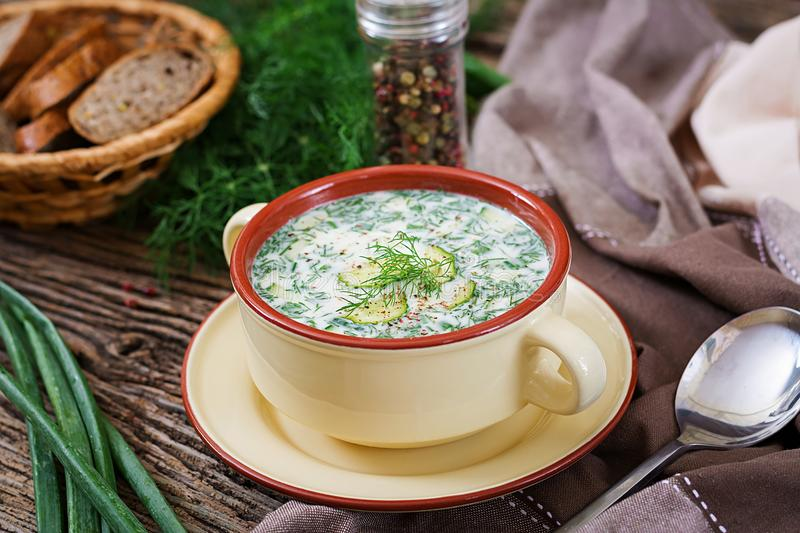 Summer yogurt cold soup with egg, cucumber, and dill on wooden table. Okroshka. Russian food royalty free stock photos