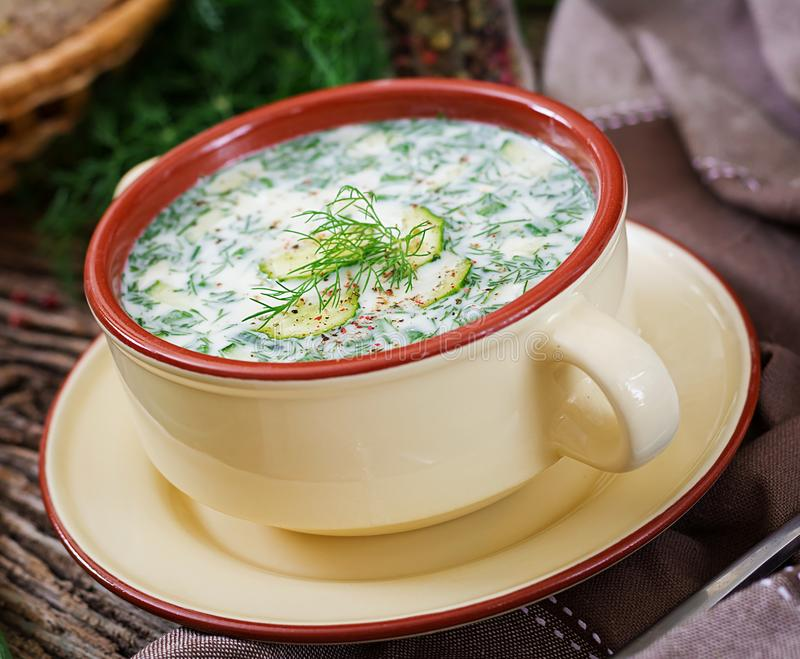 Summer yogurt cold soup with egg, cucumber, and dill on wooden table. Okroshka. Russian food royalty free stock images