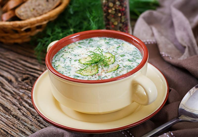 Summer yogurt cold soup with egg, cucumber, and dill on wooden table. Okroshka. Russian food stock image