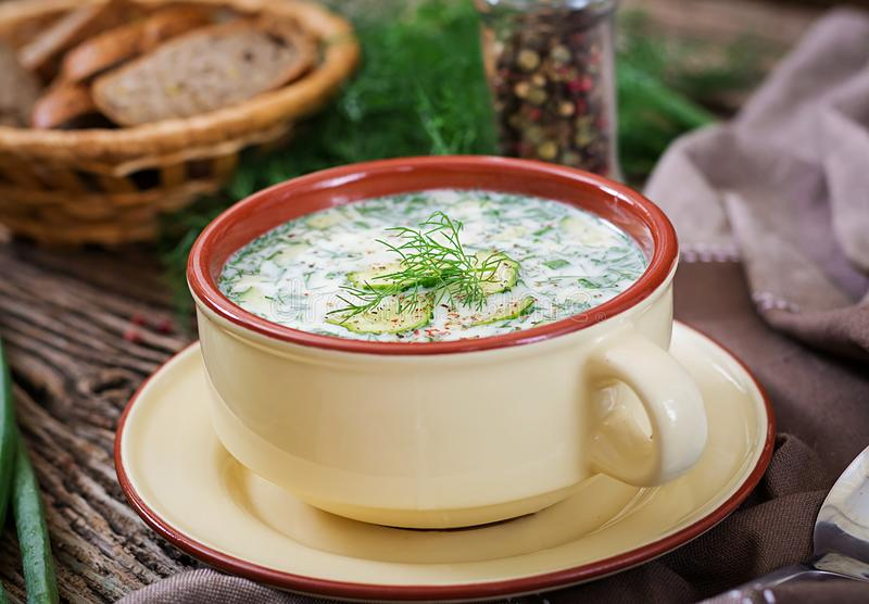 Summer yogurt cold soup with egg, cucumber, and dill on wooden table. Okroshka. Russian food royalty free stock image