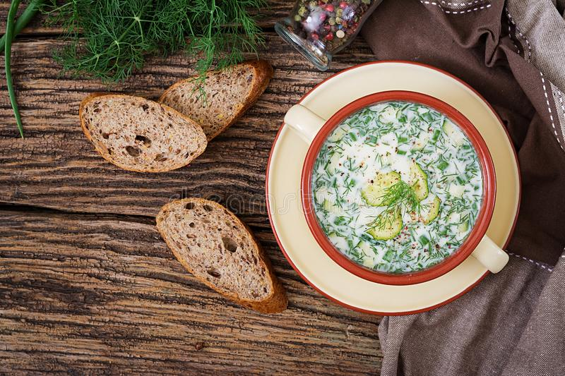 Summer yogurt cold soup with egg, cucumber, and dill on wooden table. Okroshka. Russian food. Top view. Flat lay royalty free stock images