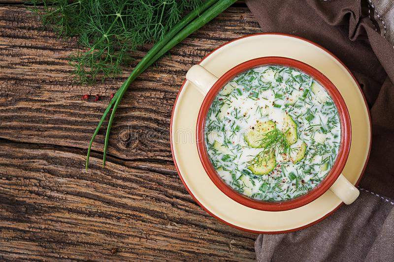 Summer yogurt cold soup with egg, cucumber, and dill on wooden table. Okroshka. Russian food. Top view. Flat lay stock photography