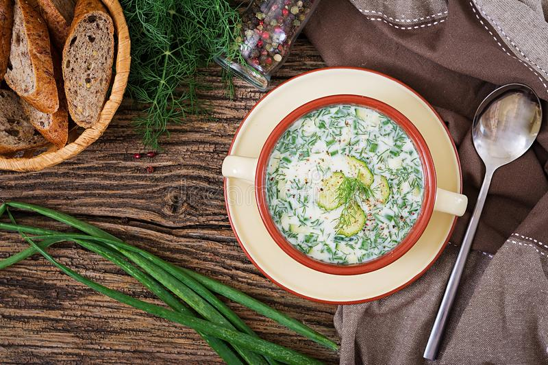 Summer yogurt cold soup with egg, cucumber, and dill on wooden table. Okroshka. Russian food. Top view. Flat lay royalty free stock photo