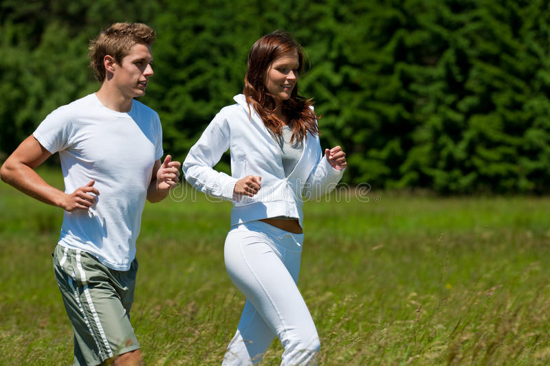 Summer - Young couple running in meadow stock image