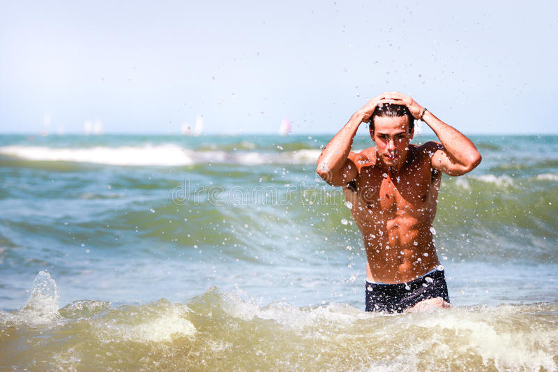 Summer. Young model man on vacation at sea. A handsome muscular guy is taking a bath in the sea. Hands through his hair. Splashing in the waves royalty free stock image