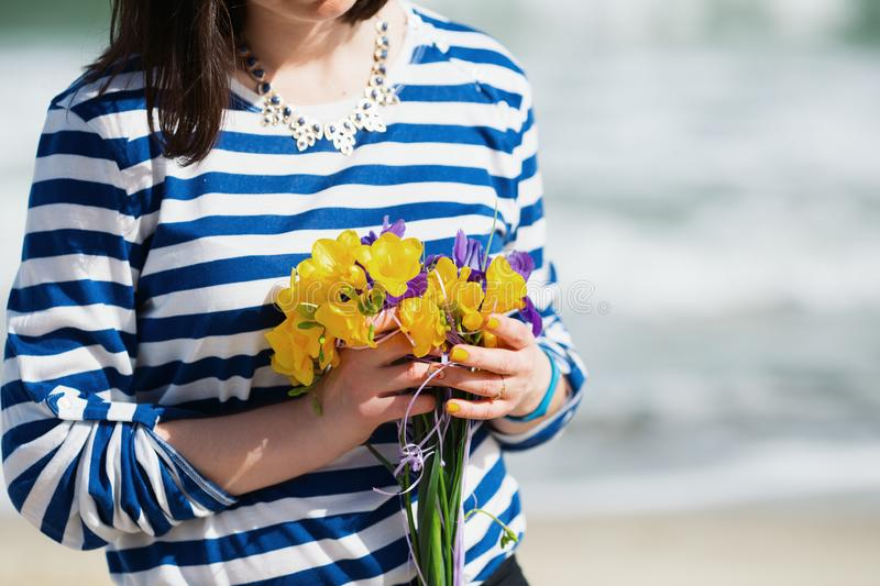Summer young woman in stripped vest with vibrant bouquet of yellow freesias and irises on seaside. Summer look on sunny day, with copy space royalty free stock photo