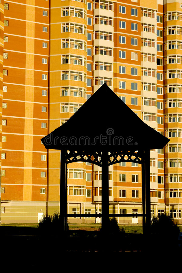 Summerhouse delante de un edificio multistoried fotografía de archivo libre de regalías