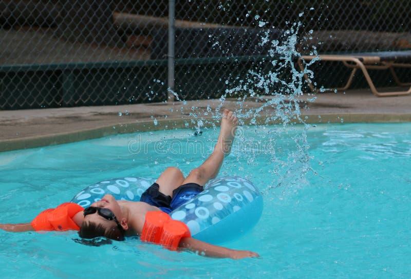Boy in pool floating kicking stock photos