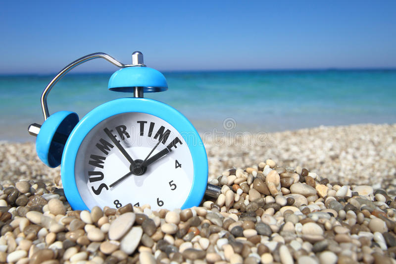 Summertime. Alarm clock on the beach royalty free stock images