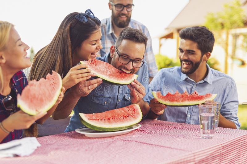 Summertime backyard party. Group of friends having an outdoor lunch, eating fresh watermelon slices and having fun stock photos