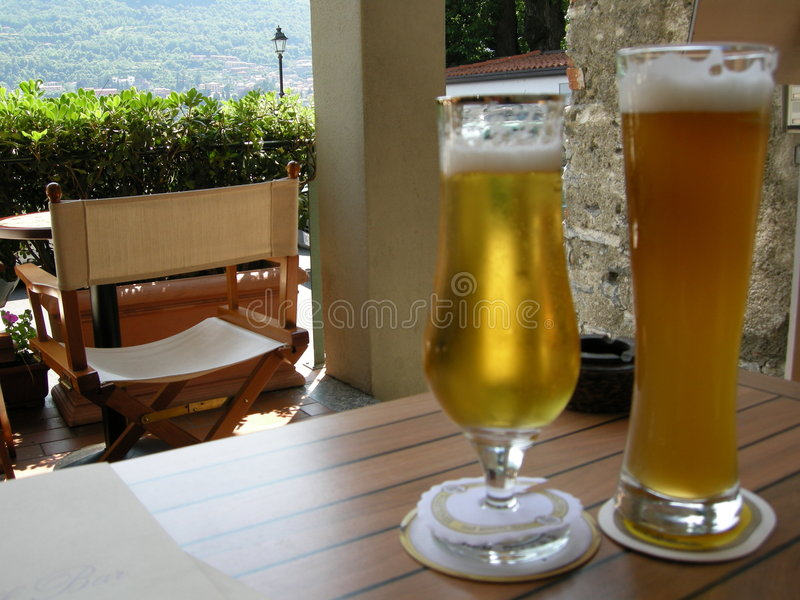 Summertime cold beers outdoors. An outdoor restaurant, with two cold frosted beers waiting on an outdoor resturant table in hot sunny southafrica royalty free stock photography