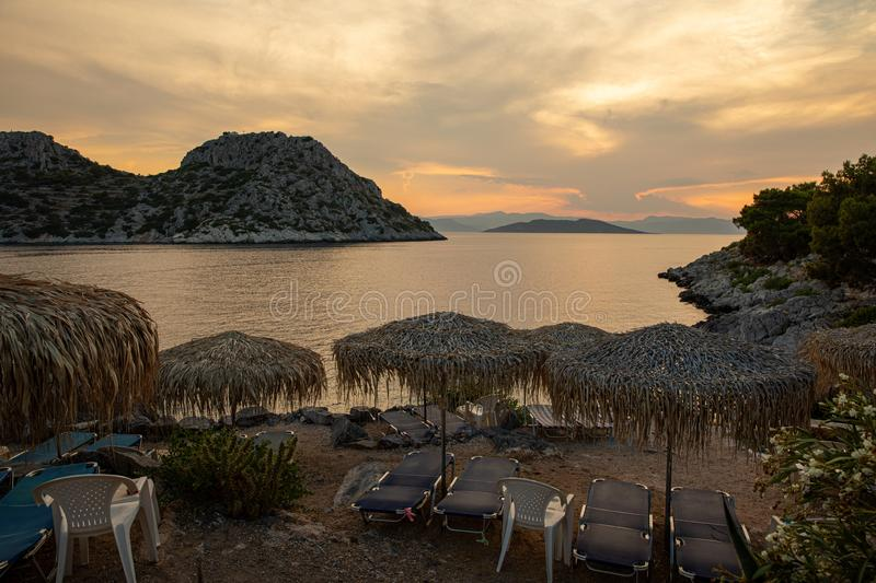 Summertime evening straw umbrellas and sun beds beautiful view from the beach of Aponissos, Agistri island, Saronic gulf. Greece. Picturesque seascape during royalty free stock images