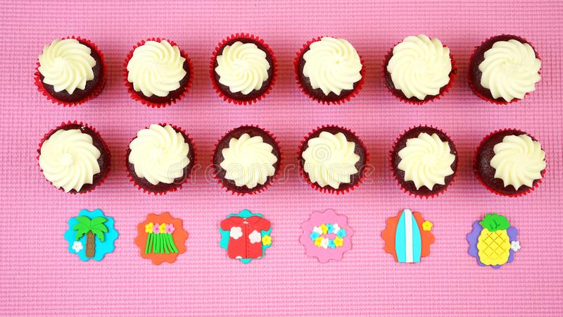 Summertime flat lay concept with tropical vacation theme cupcakes. Summertime flat lay concept with tropical vacation theme cupcakes on pink background royalty free stock photos