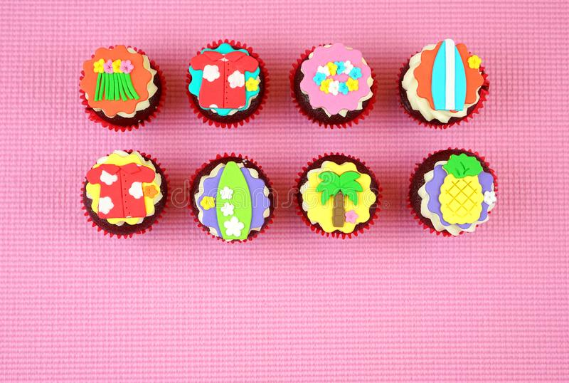 Summertime flat lay concept with tropical vacation theme cupcakes. Summertime flat lay concept with tropical vacation theme cupcakes on pink background royalty free stock photography