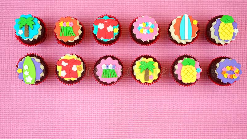 Summertime flat lay concept with tropical vacation theme cupcakes. Summertime flat lay concept with tropical vacation theme cupcakes on pink background stock photo