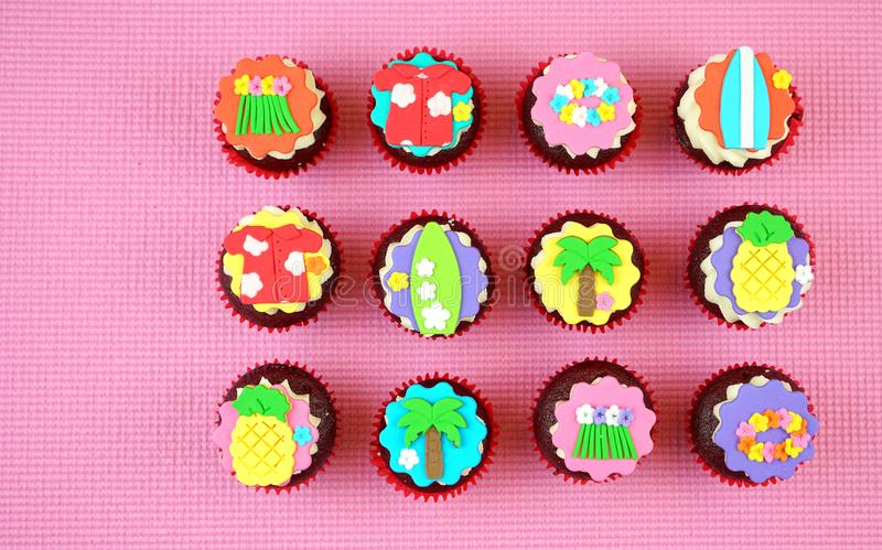 Summertime flat lay concept with tropical vacation theme cupcakes. Summertime flat lay concept with tropical vacation theme cupcakes on pink background royalty free stock images