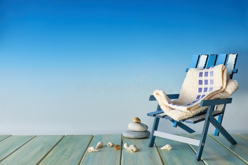 Beach chair on wooden terrace with sea shells, seaside decorations, copy-space on blue background stock images