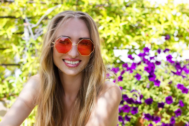 Summertime holidays. Close-up woman happy face in pink sunglasses at garden background. Summer fun weekend. Beautiful girl. With perfect white teeth smile royalty free stock image