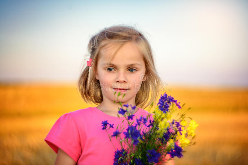 Summertime. A little girl holding a bunch of wild flowers stock images