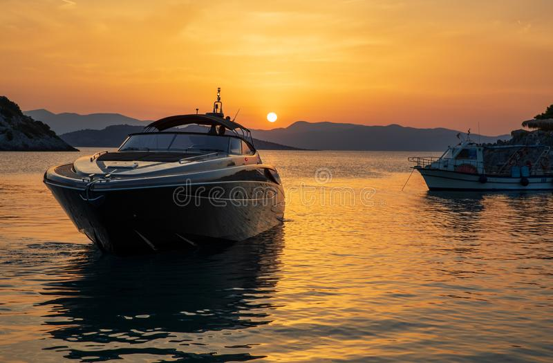 Summertime luxury yacht at sunset as seen from the beach of Aponissos, Agistri island, Saronic gulf, Greece. Horizontal stock images