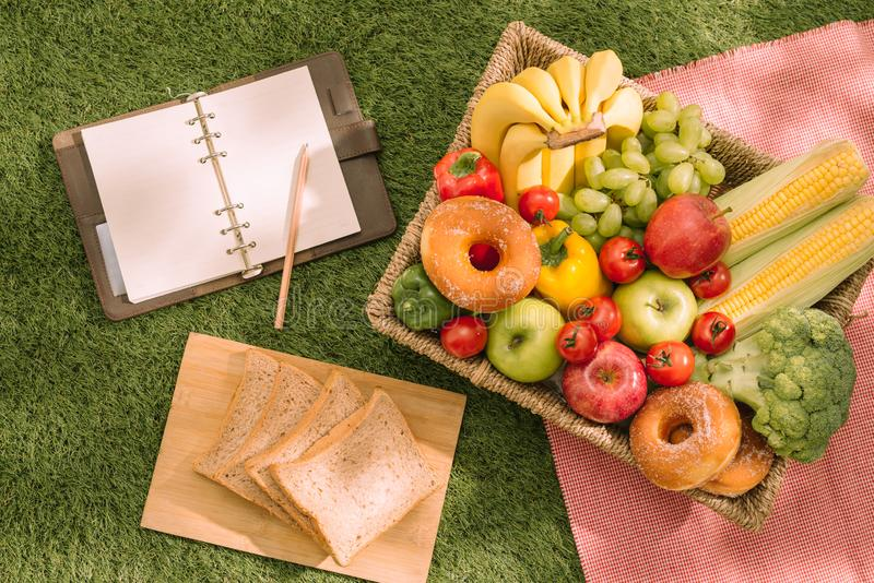 Summertime picnic setting on the grass with open picnic basket, fruit, salad and cherry pieå royalty free stock images